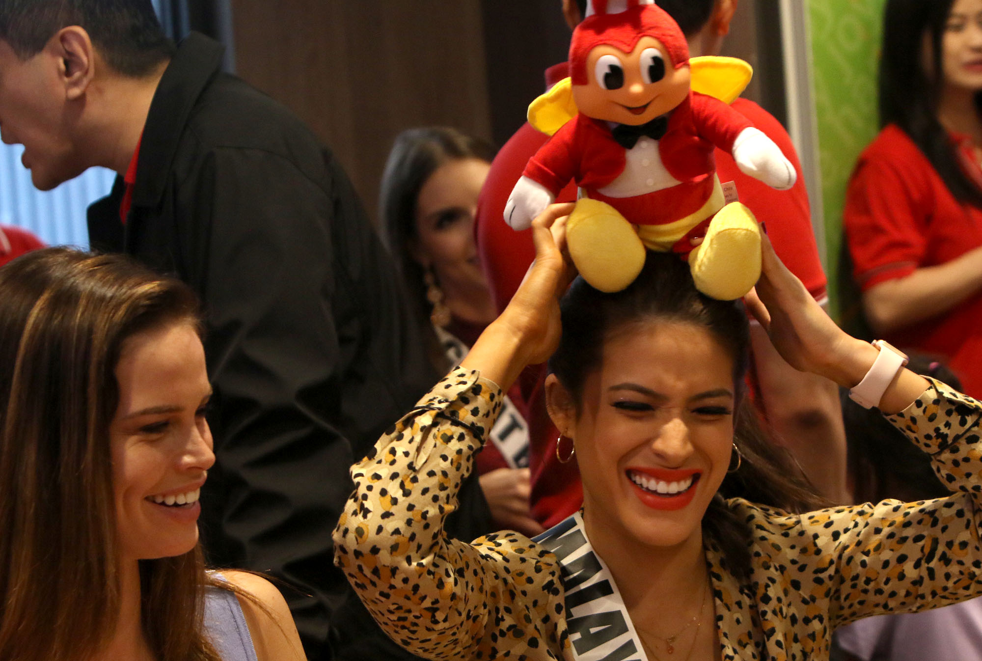 Malaysia's Samantha James crowns herself with a Jollibee stuffed toy to the amusement of Netherlands' Nicky Opheij