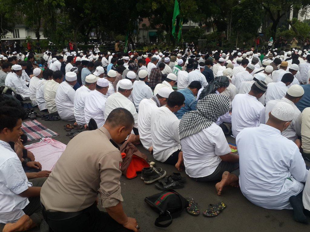 Seorang polisi ini salat Jumat bersama peserta aksi demo di depan Istana Negara. Foto oleh Uni Lubis/Rappler