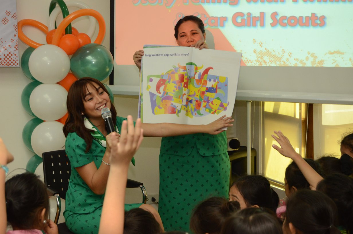 STORYTELLING. Kathryn reads a book to a group of Girl Scouts. Photo from Facebook/Girl Scouts of the Philippines