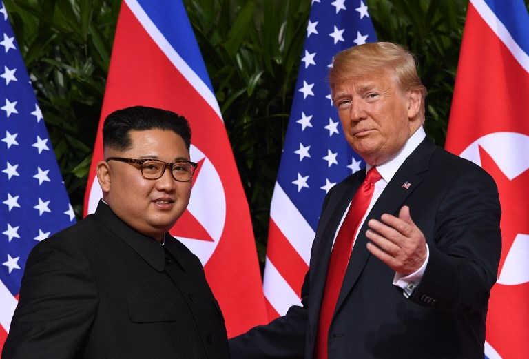 FIRST. US President Donald Trump (R) gestures as he meets with North Korea's leader Kim Jong Un (L) at the start of their historic US-North Korea summit, at the Capella Hotel on Sentosa island in Singapore on June 12, 2018. Photo by Saul Loeb/AFP
