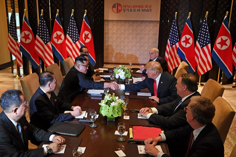 NEGOTIATION. US President Donald Trump (3rd R) shakes hands with North Korea's leader Kim Jong Un (3rd L) as they sit down with their respective delegations for the US-North Korea summit, at the Capella Hotel on Sentosa island in Singapore on June 12, 2018. Photo by Saul Loeb/AFP