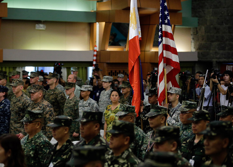SHOULDER-TO-SHOULDER. Military troops from the Philippines and United States hold up their respective national flags during opening rites of the Philippines-US Exercise Balikatan in Quezon City on April 20 2015.  Photo by Ritchie Tongo/EPA