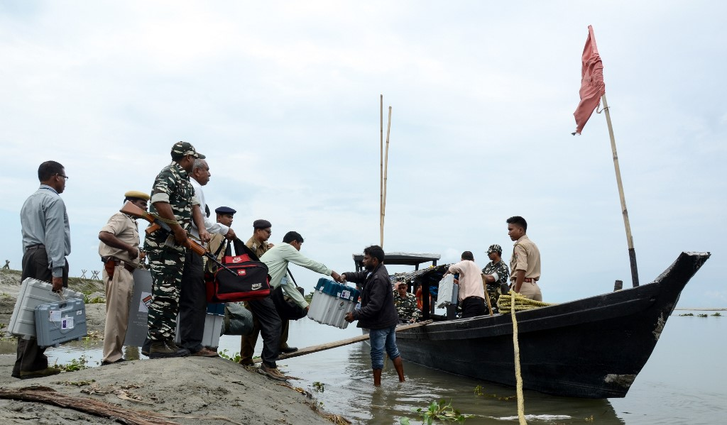 BEFORE ELECTIONS. Indian election officials carry Electronic Voting Machines on a boat, as security personnel watch over, to reach remote polling stations, in Dibrugarh, some 480 kms from Guwahati in the northeastern state of Assam on April 10, 2019. Photo by STR/AFP