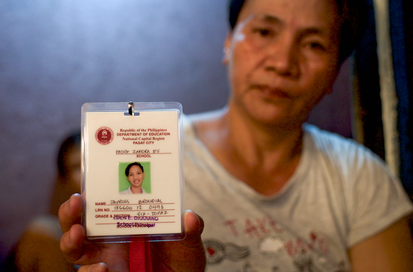 GRADE 6. Rosana holds the school ID of her son Jayross or Utoy. The 13-year-old was set for graduate from grade school in March 2018. Photo by Eloisa Lopez/Rappler