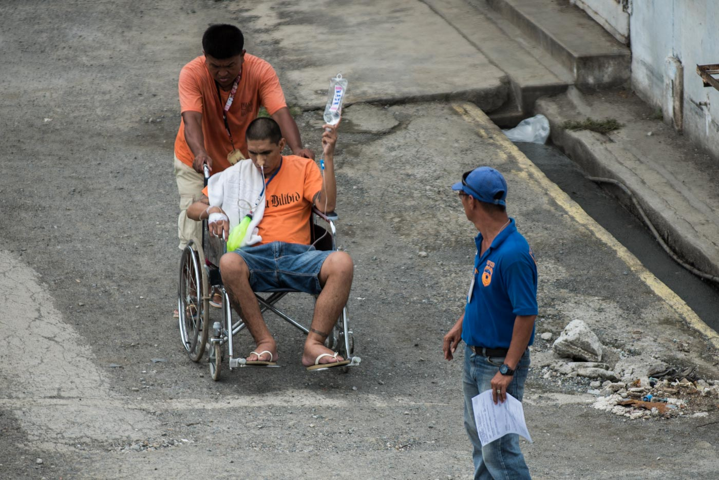 MEDICAL CARE NEEDED. A sick inmate's wheelchair is being pushed by another prisoner under the heat of the sun. Photo by Lisa Marie David/Rappler