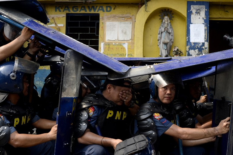 VIOLENT CONFRONTATION. Policemen use their shields at the demolition of an informal settler community in Caloocan City on May 26, 2015. Some 500 families were affected. Photo by Noel Celis/AFP