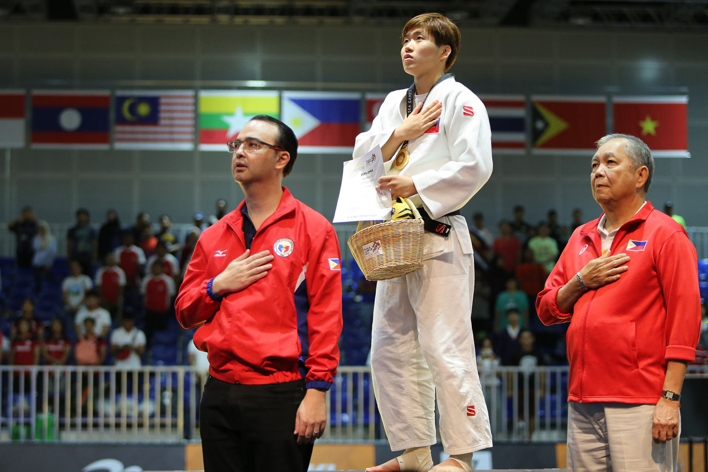 NATIONAL ANTHEM. Kiyomi Watanabe of the Philippines clinches the gold medal in the women's -63kg judo event. She is seen here during the Philippine national anthem with Philippine officials. Photo by PSC-POC Media Group
