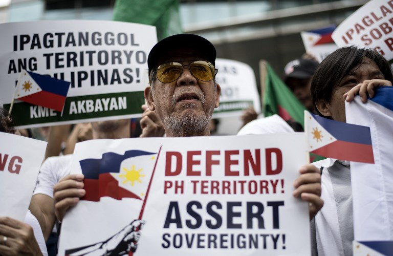 FIGHT. Activists participate on a protest in front of the Chinese Consular office in Manila on July 12, 2018, to mark the second anniversary of a UN-backed tribunal ruling in July 2016 saying there was no basis for China's claims to most of the South China Sea. All photos by Noel Celis/AFP