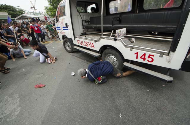 VIOLENCE. A man is seen stuck under the police vehicle on October 19. Photo by Rob Reyes