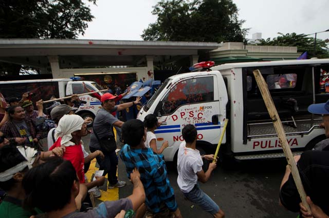 COUNTER-ATTACK. Activists attack the police vehicle after it ran over protesters in front of the US embassy. Photo by Rob Reyes/Rappler