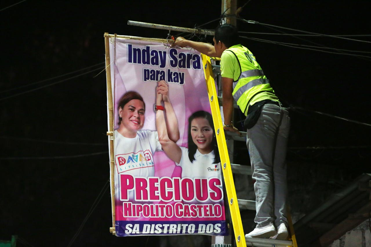 HAZARD. Posters that pose as hazards to commuters and residents are dismantled. Photo by Ben Nabong/Rappler