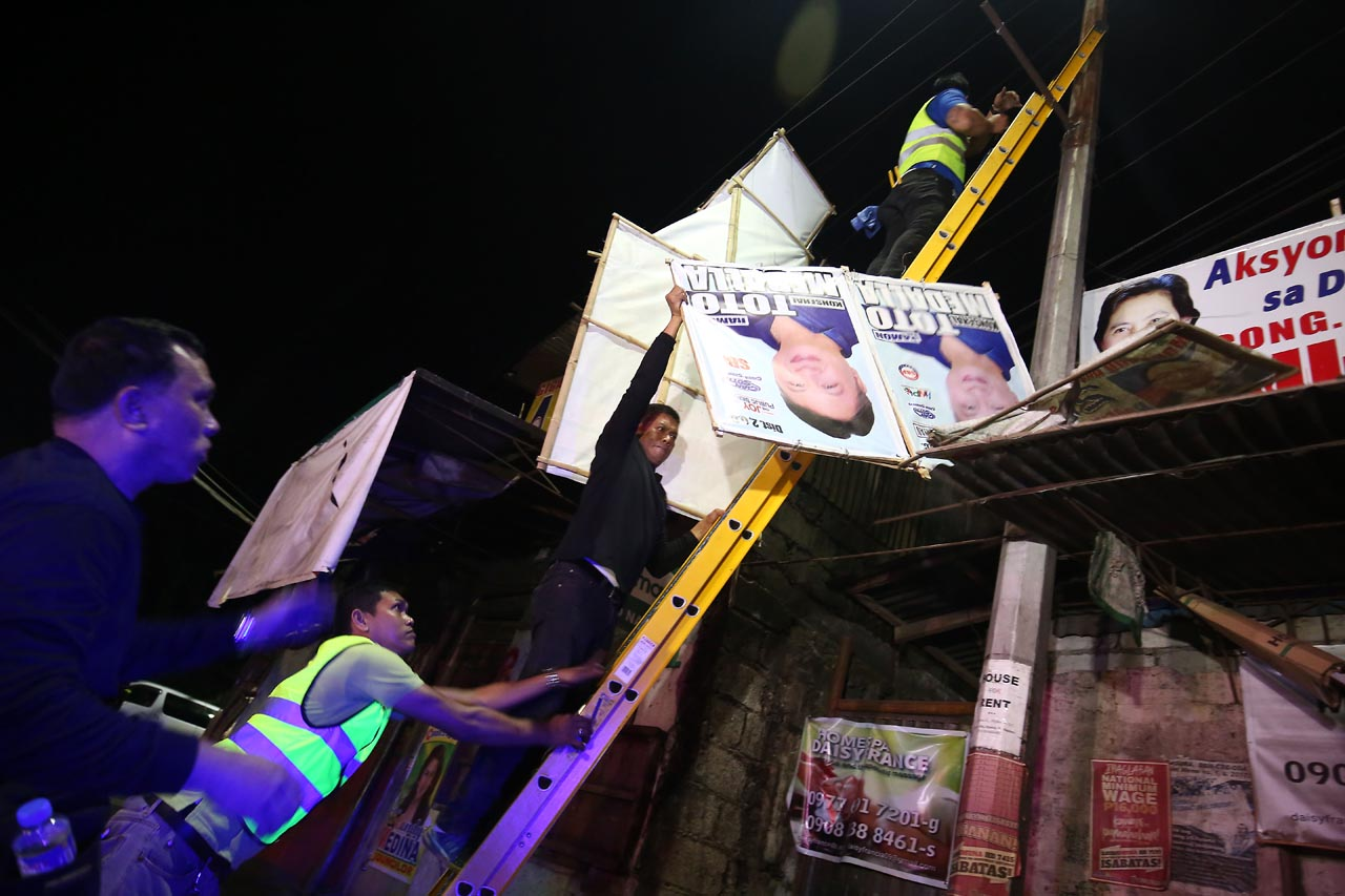 HAZARD. Campaign posters placed in illegal areas are taken down to prevent danger to lives and properties. Photo by Ben Nabong/Rappler