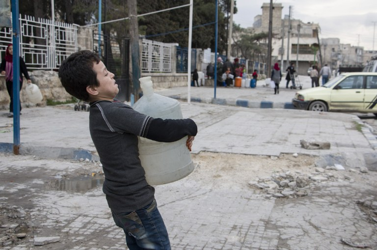 DAILY STRUGGLE. A Syrian boy carries a container filled with water on February 23, 2016 in the rebel-held side of the northern city of Aleppo. Photo by Karam al-Masri/AFP