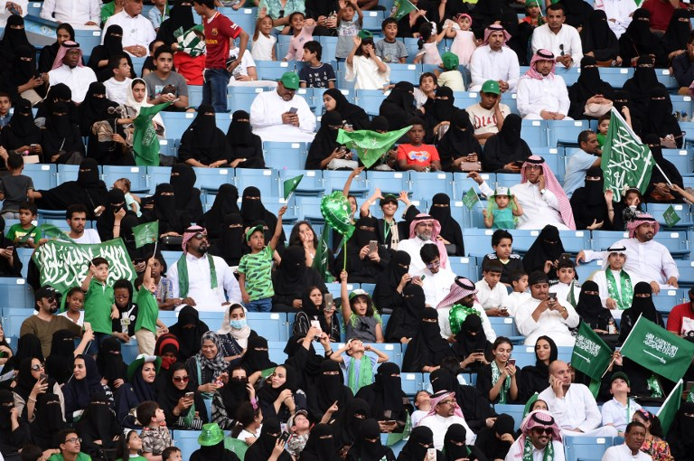 In this file photo, Saudi families sit in a stadium waving national flags, to attend an event in the capital Riyadh on September 23, 2017 commemorating the anniversary of the founding of the kingdom. Fayez Nureldine/AFP