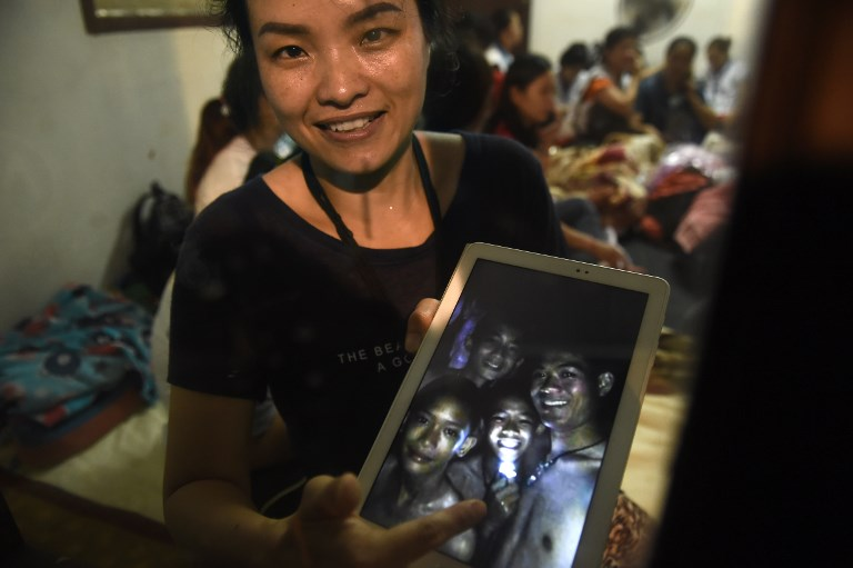 'FOUND SAFE.' A family member shows a picture of 4 of the 12 missing boys near the Tham Luang cave at the Khun Nam Nang Non Forest Park in Mae Sai on July 2, 2018. Photo by Lillian Suwanrumpha/AFP