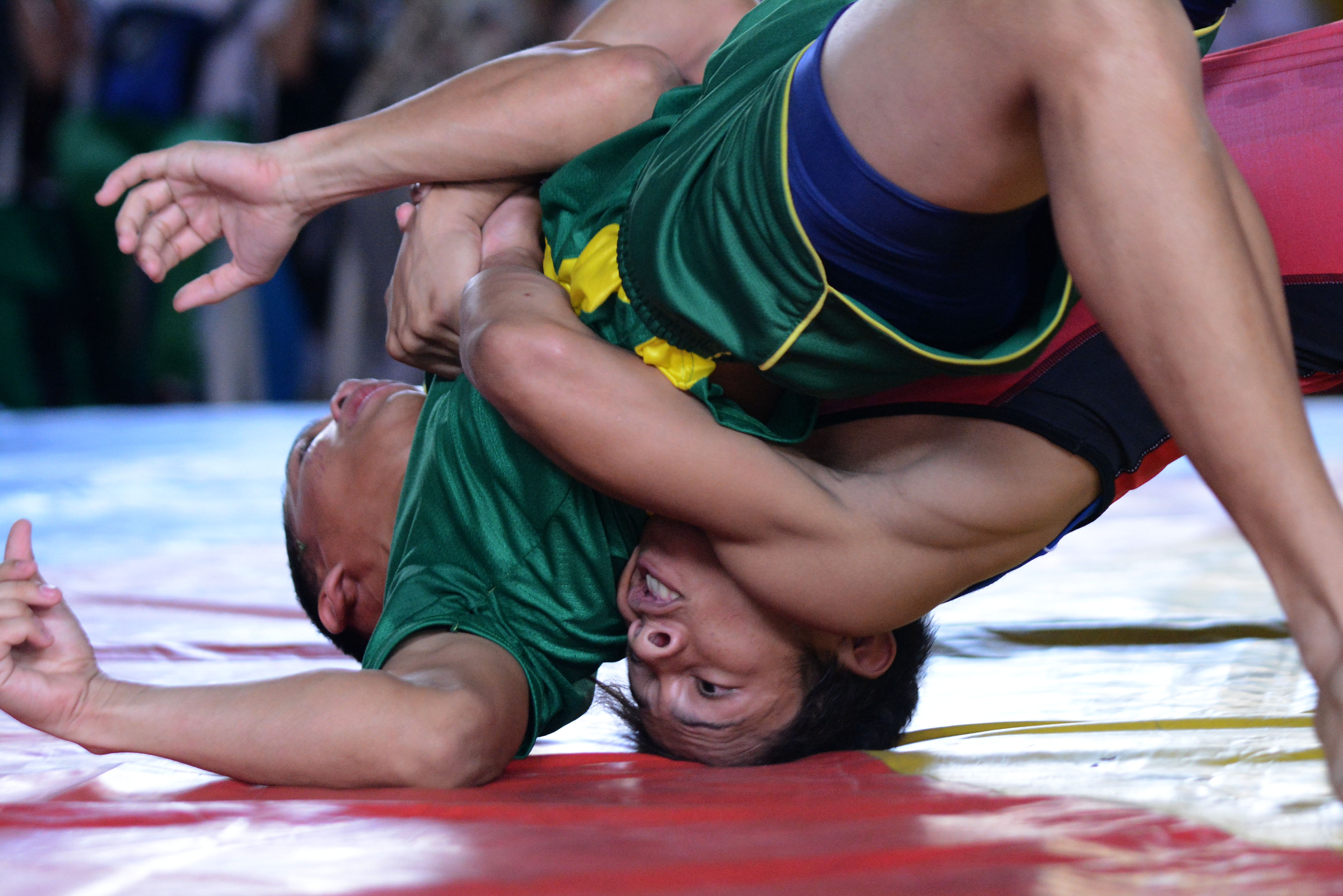 ON THE MAT. Wrestlers grapple on the mat during a match. Photo by Roy Secretario/ Rappler