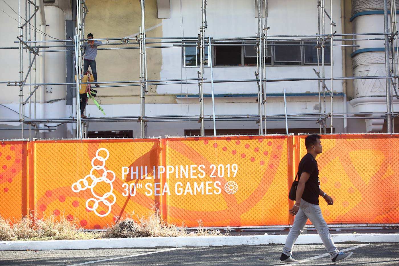LAST MINUTE. Workers are trying to complete the repainting of the facade of the Rizal Memorial Stadium on the same day it hosts the football competition. Photo by Ben Nabong/Rappler