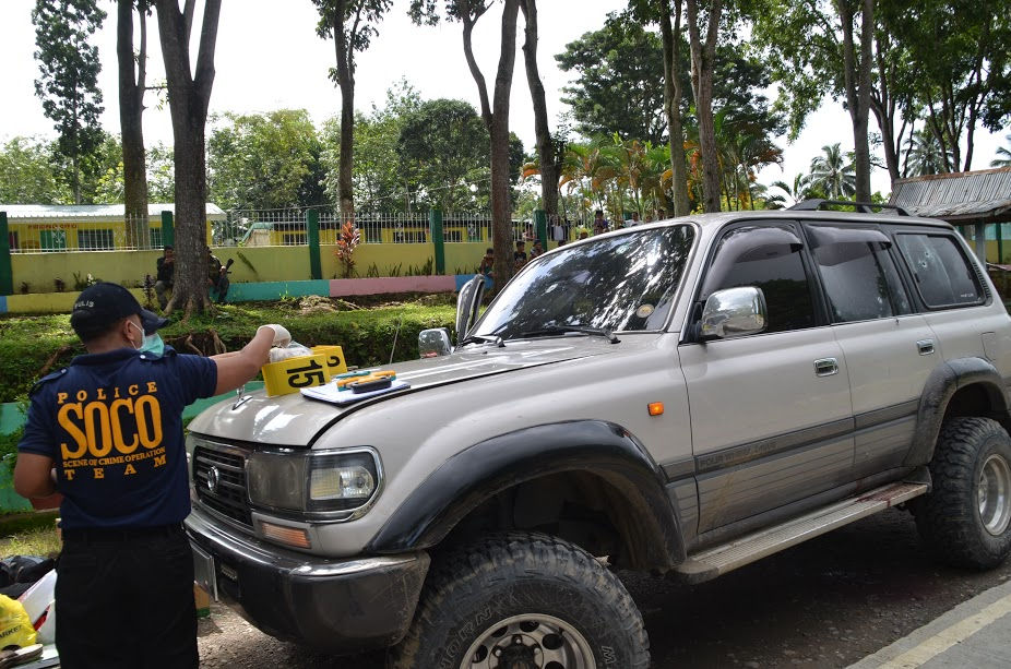 CRIME SCENE. Police crime operatives inspect one of the vehicles on the convoy. Photo courtesy of the office of Mayor Rudy Caoagdan of Makilala