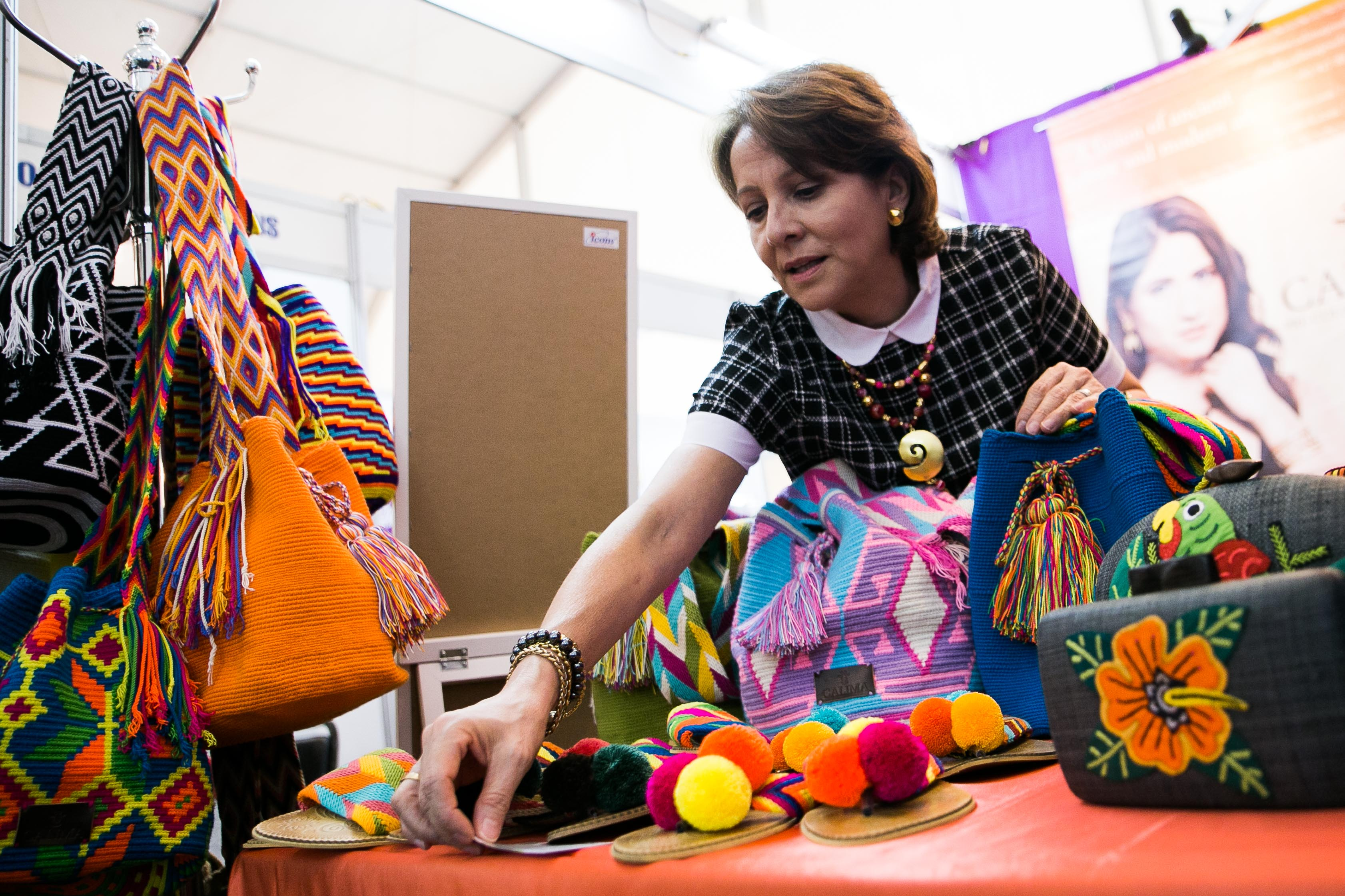 FROM CALIMA. Colombian Claudia Hernandez fixes her products at the APEC International Media Center. She sells sandals, bags, and purses made by the Wayuu tribe in Colombia, and jewelry inspired by Colombian designs. Photo by Pat Nabong/Rappler