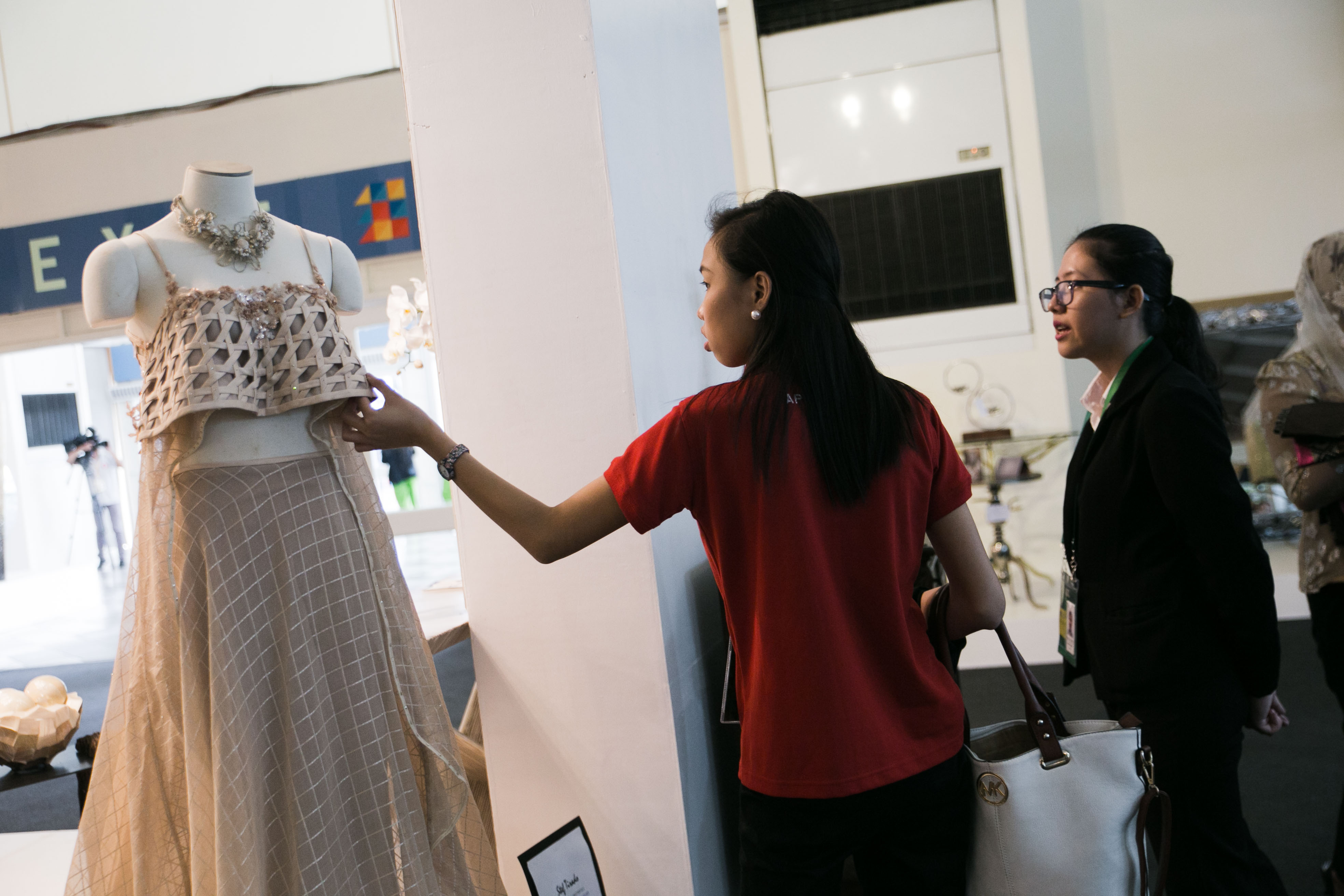 POTENTIAL BUYERS. Two women examine a gown that was exhibited by Expo Mandaue at the APEC International Media Center. Mandaue is a springboard of many businesses that hope to be and already are part of the export economy. Photo by Pat Nabong/Rappler