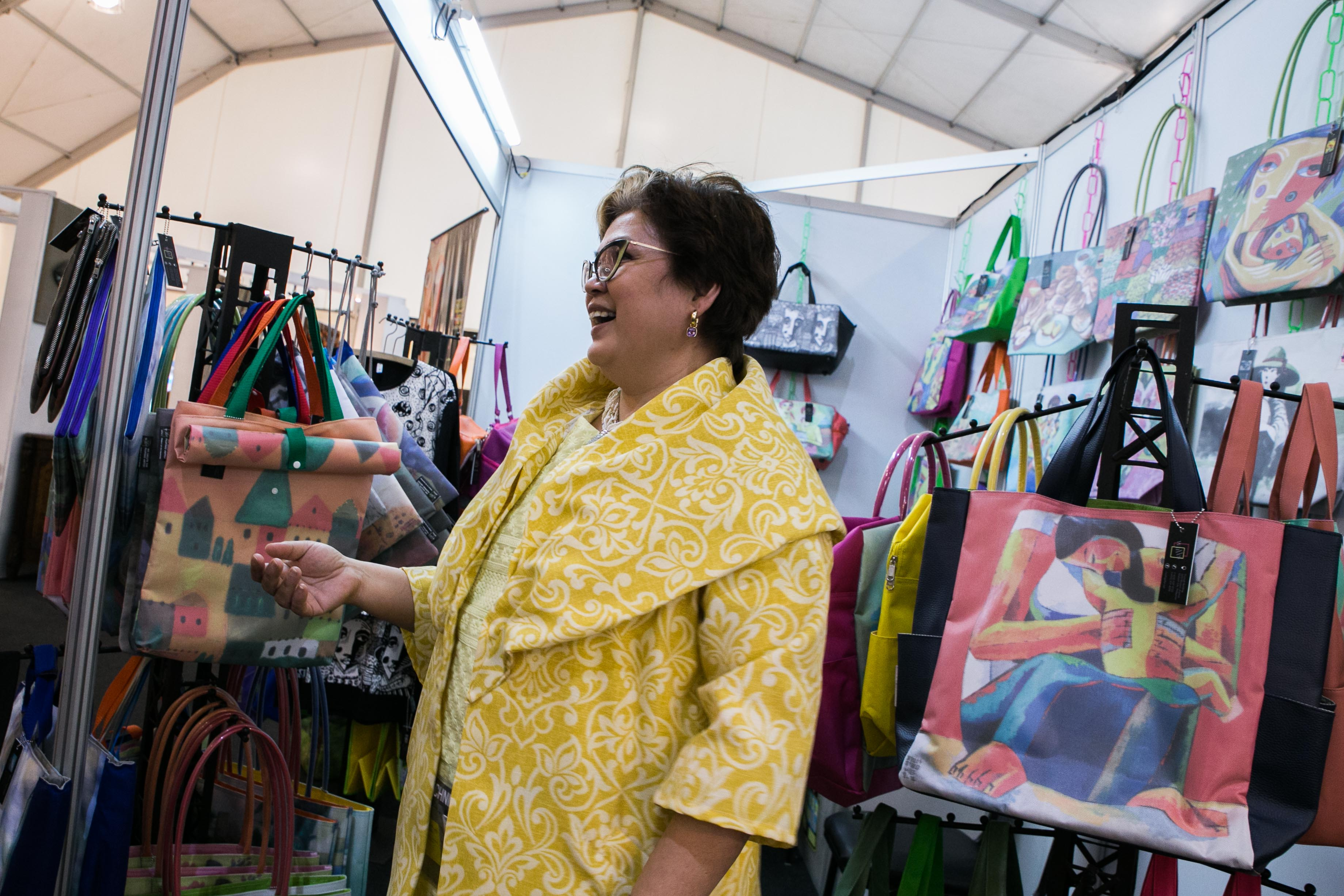 ARTS TO BAGS. Gigi Phua-Lim, an entrepreneur who started as an art collector, talks to a customer in her booth at the APEC International Media Center. She hopes to promote Filipino artists and hopefully foreign artists through the reproduction of their works on everyday wear. Photo by Pat Nabong/Rappler