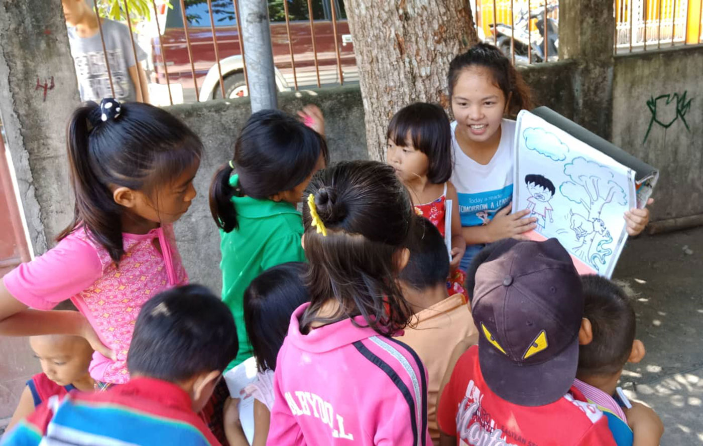 LITERACY ADVOCATE. A young volunteer teacher from San Jose Elementary School in Donsol town, Sorsogon, teaches children to read a book on the street. Photo by Rhaydz B. Barcia/Rappler