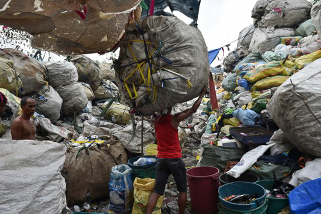 INFORMAL WORK. A worker carries a bale of collected recyclable materials at a junk shop near a former dumpsite in Manila. File photo by Ted Aljibe/AFP
