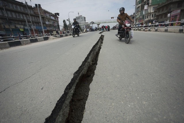 CRACKED OPEN. Motorcyclists use both sides of a wide crack in the Koteshwor-Suryabinayak Highway caused by the earthquake in the Bhaktapur area near Kathmandu, Nepal on 26 April, 2015 u2013 twenty four hours after a devastating quake which so far has taken the lives of at least 2,400. Hemanta Shrestha/EPA