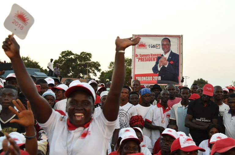 ELECTIONS. Supporters of Sierra Leone's All People's Congress (APC) presidential candidate Samura Kamara hold a campaign poster during a rally on March 3, 2018, in Kambia, ahead of the country's general election. Photo by Issouf Sanogo/AFP