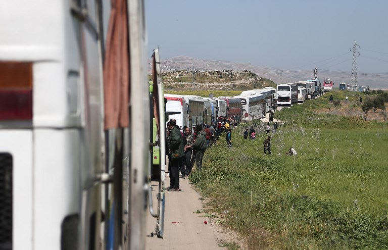 FLEEING GHOUTA. A convoy transporting Syrian civilians and rebel fighters evacuated from Eastern Ghouta waits in a government-held area prior to entering the village of Qalaat al-Madiq, some 45 kilometres northwest of the central city of Hama, on March 26, 2018, as evacuations from the opposition enclave continued following a deal that was announced earlier in the week. Photo by Abdulmonam Eassa/AFP