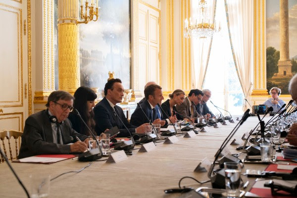 Members of the commission convene in Paris on September 11, 2018 with French President Emmanuel Macron to discuss the multilateral approach to combating fake news around the world. Photo by Yann Stofer