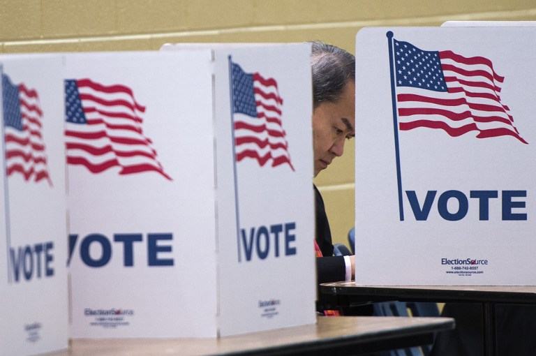 A man votes at a polling place at a high school in McLean, Virginia during the US presidential election on November 8, 2016. Andrew Caballero-Reynolds/AFP