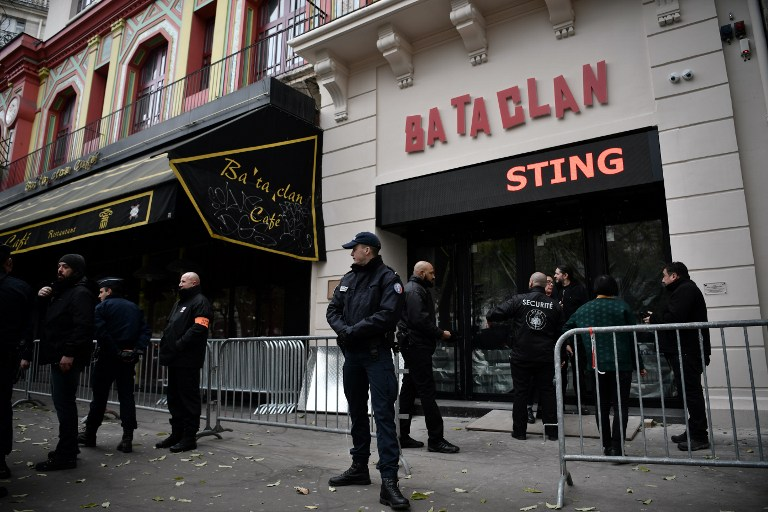 UNDER HEAVY GUARD. French policemen and security officers stand guard at the entrance of the Bataclan concert hall in Paris on November 12, 2016, a few hours before the reopening concert by British musician Sting to mark the first anniversary of the November 13 Paris attacks. Photo by Philippe Lopez/AFP