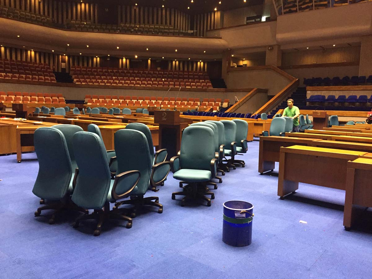 REARRANGING. A man rearranges the chairs and tables usually used by lawmakers during the cleaning preparations at the Batasang Pambansa. Photo by Mara Cepeda/Rappler