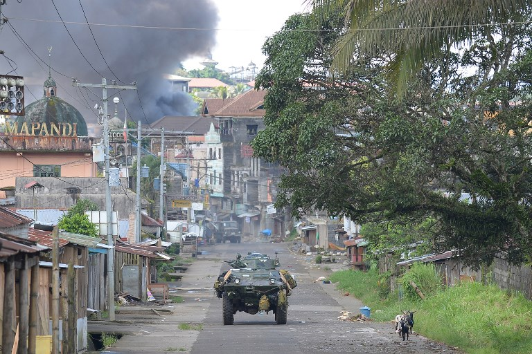 In this file photo, a Philippine Marines armored personnel carrier speeds away as black smoke billows from burning houses after military helicopters fired rockets at militant positions in Marawi on the southern island of Mindanao on May 30, 2017. Ted Aljibe/AFP