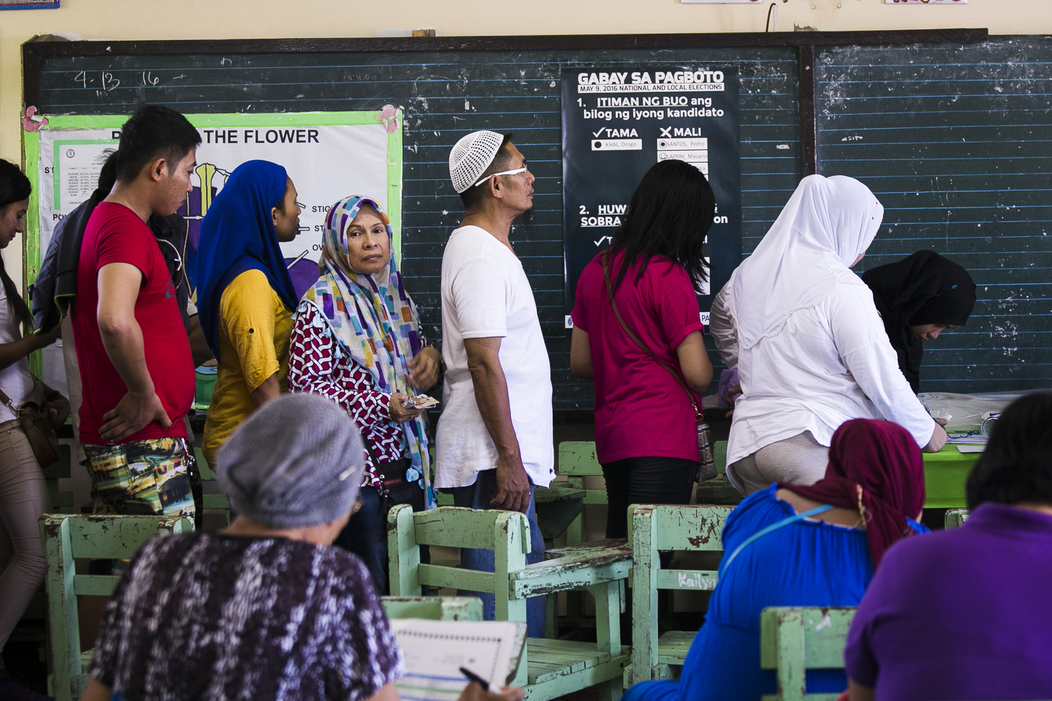 QUEUE. Voters wait for their turn to vote as one of the machines in Maharlika Elementary School malfunctions. Photo by Pat Nabong/Rappler