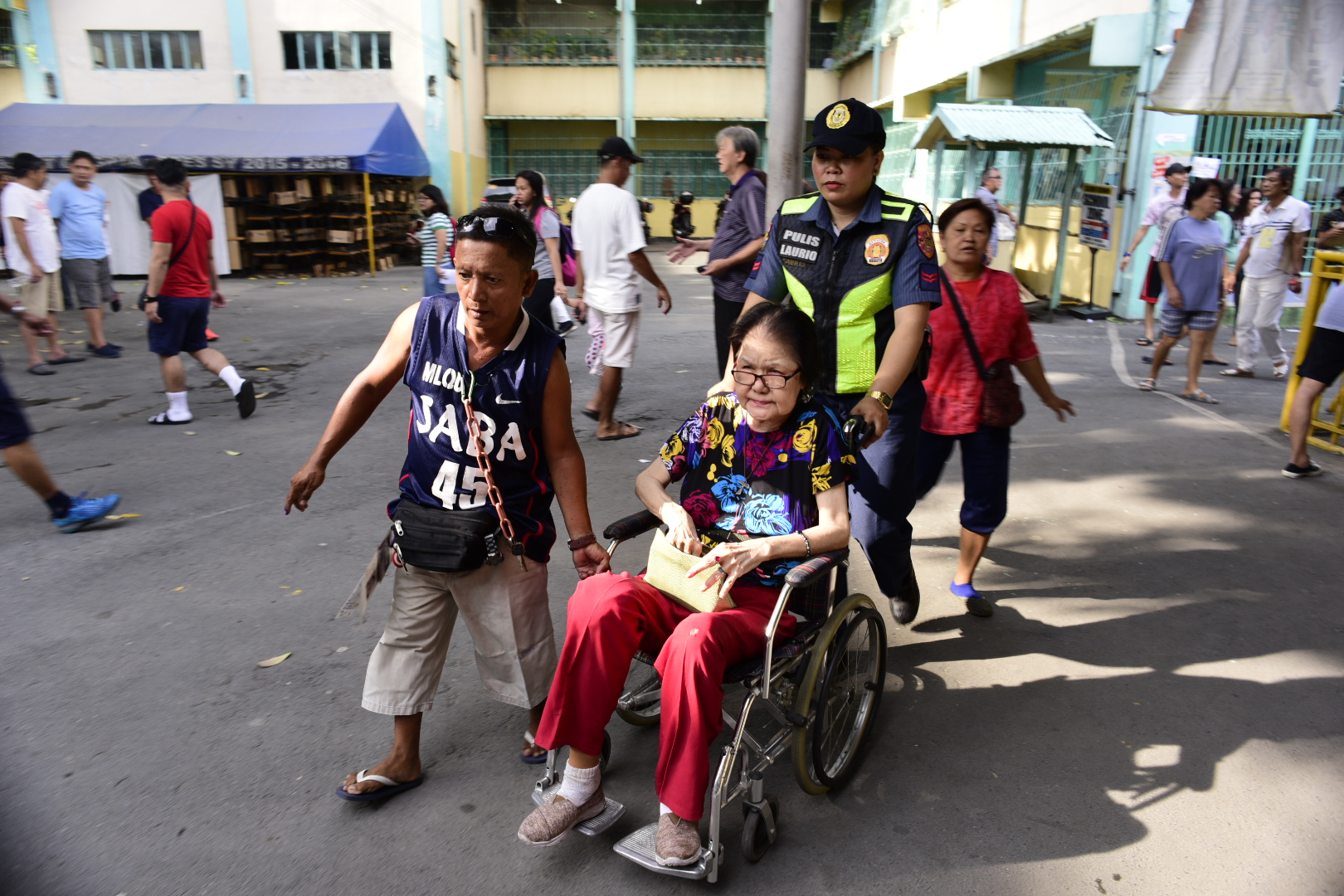 PASAY. A police officer assists a PWD at P Burgos Elementary School. Photo by Rob Reyes/Rappler