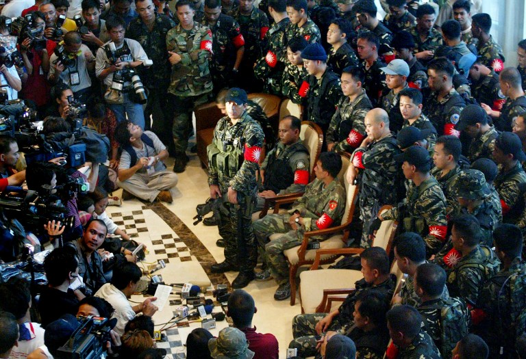 MUTINY. A group of rebel troops and officers belonging to elite military units face journalists as they wait for the 5:00 pm deadline for their surrender inside the Oakwood Hotel in the suburban financial district of Makati in Manila, 27 July 2003. Photo by Jimin Lai/AFP