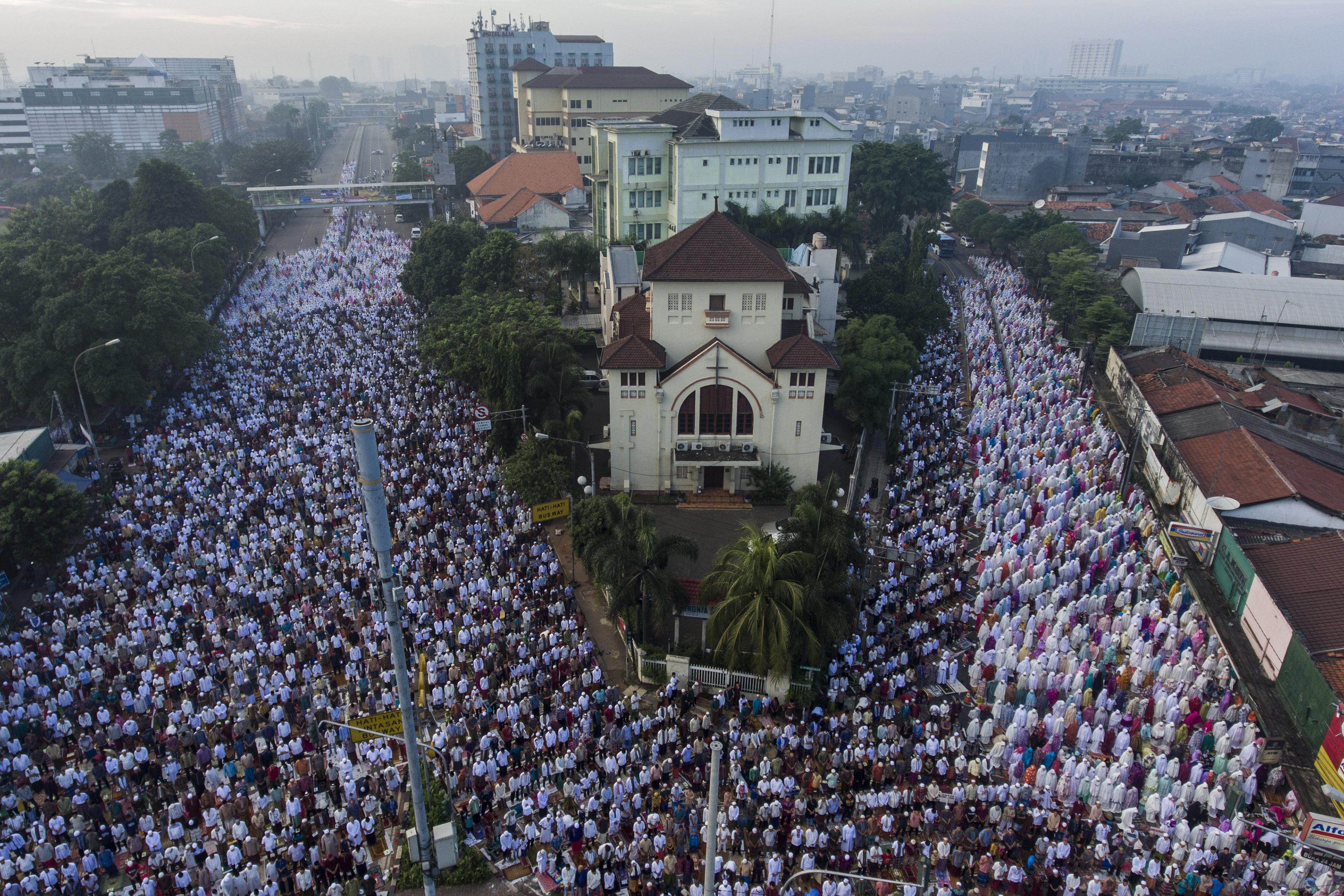 RIBUAN UMAT MUSLIM SALAT. Foto aerial ribuan umat muslim mengikuti salat Idul Fitri 1438 H di Jatinegara, Jakarta Timur, Minggu, 25 Juni. Foto oleh Sigid Kurniawan/ANTARA
