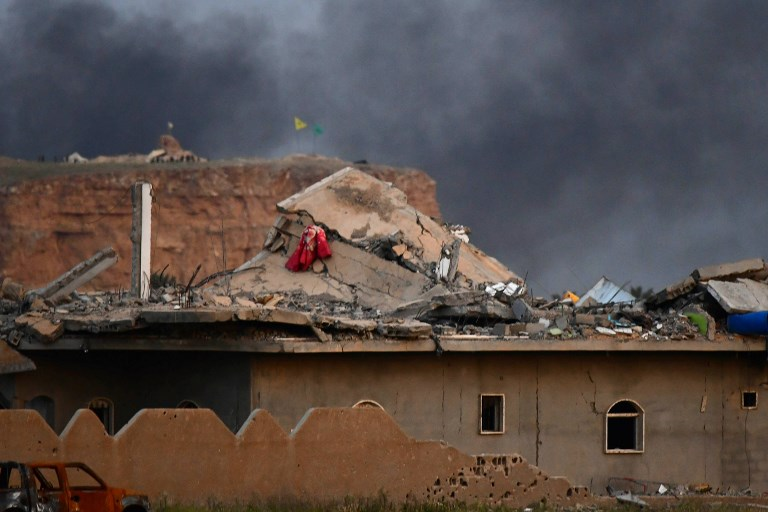 DAMAGE. This picture taken on March 22, 2019 shows the damaged roof of a building with smoke rising over the village of Baghouz with the flags of the Kurdish People's Protection Units (Yellow) and Women's Protection Units (Green) seen flying in the background. Photo by Giuseppe Cacace/ AFP