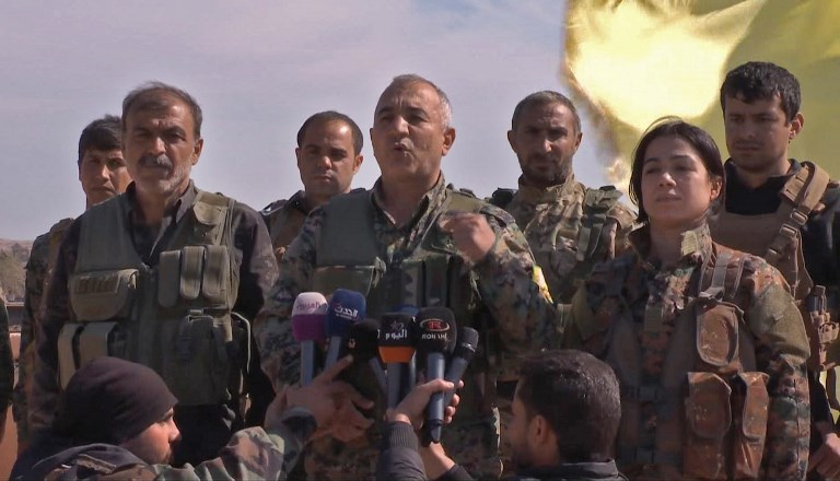 SDF. An image grab released by the Kurdish Ronahi TV on March 23, 2019 shows the US-backed Syrian Democratic Forces (SDF) assault's overall commander Jia Furat (center) delivering a speech after announcing the total elimination of the Islamic State group's last bastion of Baghuz. (Photo by Ronahi TV/AFP
