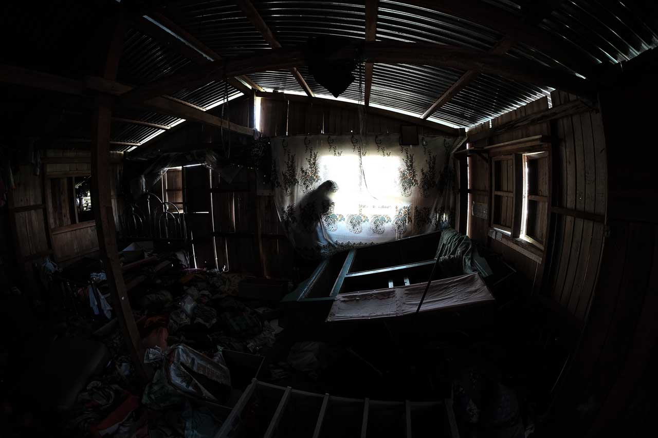 LET THE SUNSHINE IN. 70-year-old  Cayaranao Mangandiri opens the window of her looted house along Cabili Street in Barangay Daguduban. Photo by Bobby Lagsa/Rappler