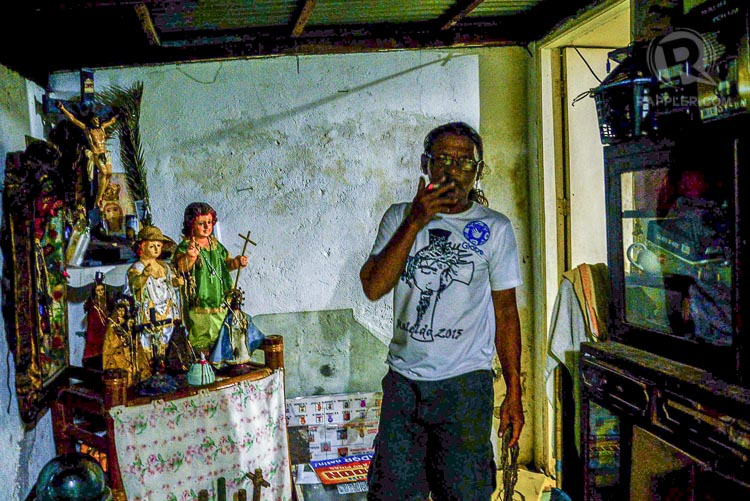 BEHIND THE LIGHT. Ben Kristo smokes beside the religious icons inside their home in San Pedro Cutud, San Fernando, Pampanga. All Photos by Jansen Romero/Rappler
