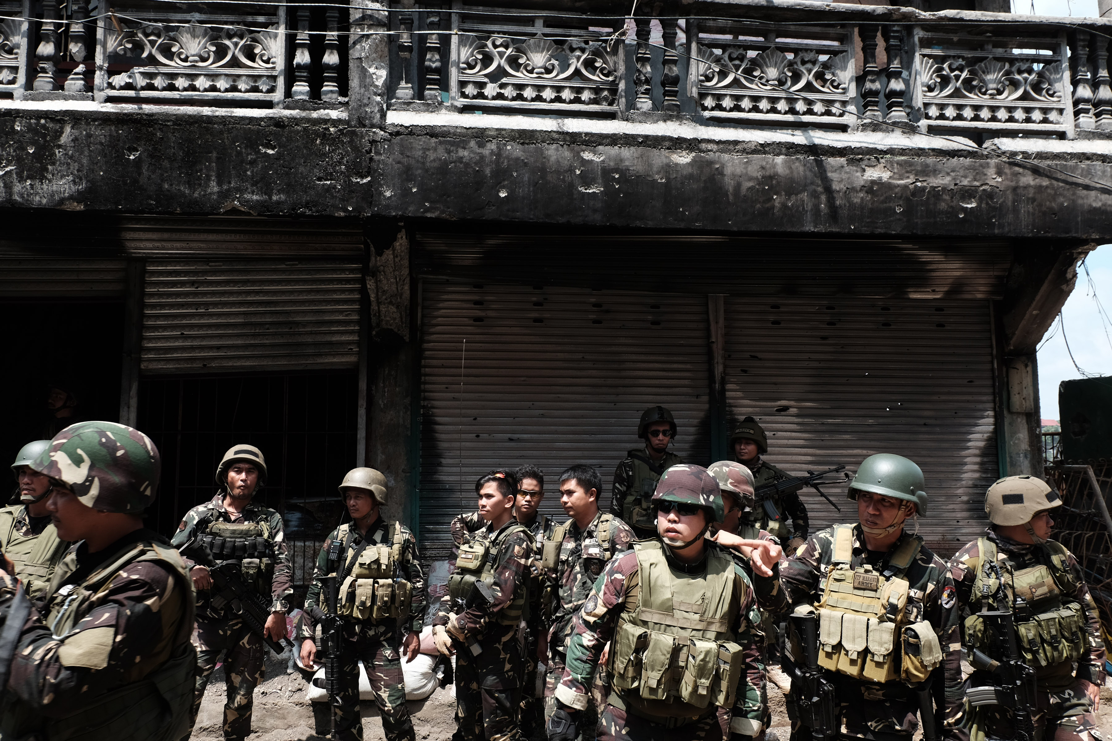 Soldiers stand outside a cleared building near Mapandi bridge. Photo by Bobby Lagsa/Rappler