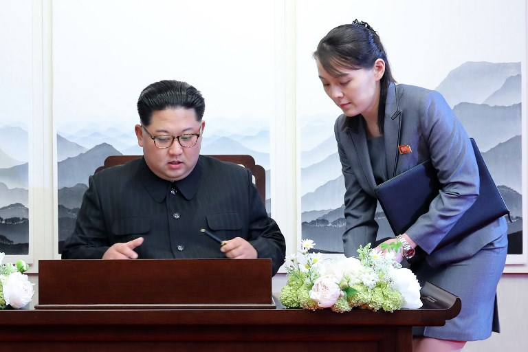 'A NEW HISTORY.' North Korea's leader Kim Jong Un (L) signs the guest book next to his sister Kim Yo Jong (R) during the Inter-Korean summit with South Korea's President Moon Jae-in at the Peace House building on the southern side of the truce village of Panmunjeom on April 27, 2018. AFP PHOTO / Korea Summit Press Pool