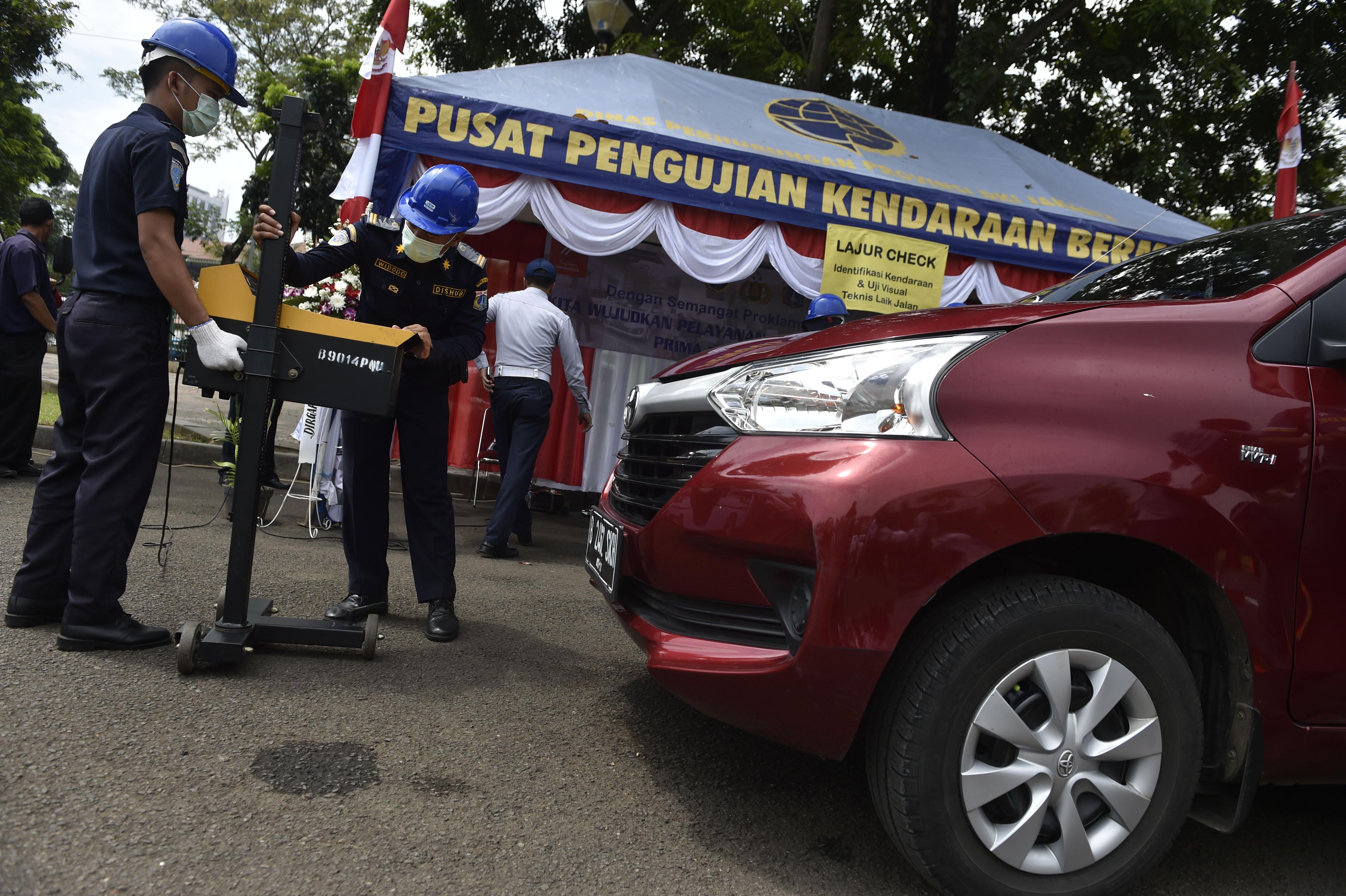 Petugas melakukan pengecekan kendaraan saat berlangsung layanan uji SIM A Umum dan Ujian Berkala (KIR) angkutan umum berbasis online serta taksi umum di Silang Monas, Jakarta, pada 15 Agustus 2016. Foto oleh Puspa Perwitasari/Antara
