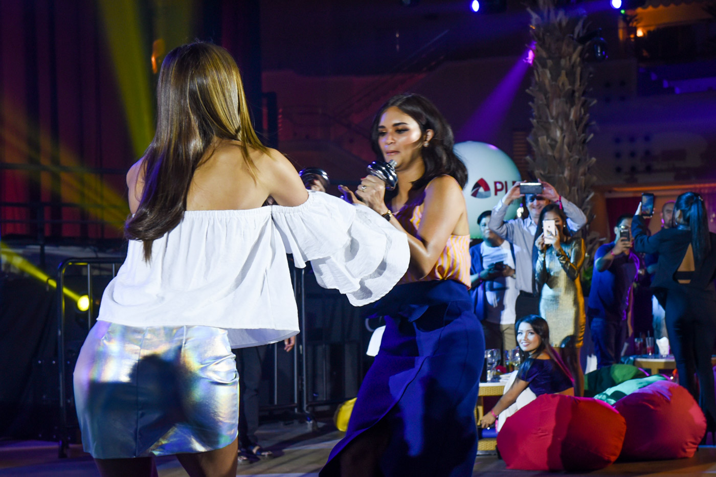 READY GO! Pia Wurtzbach passes a set of weights to Iris Mittenaere during the grit challenge.