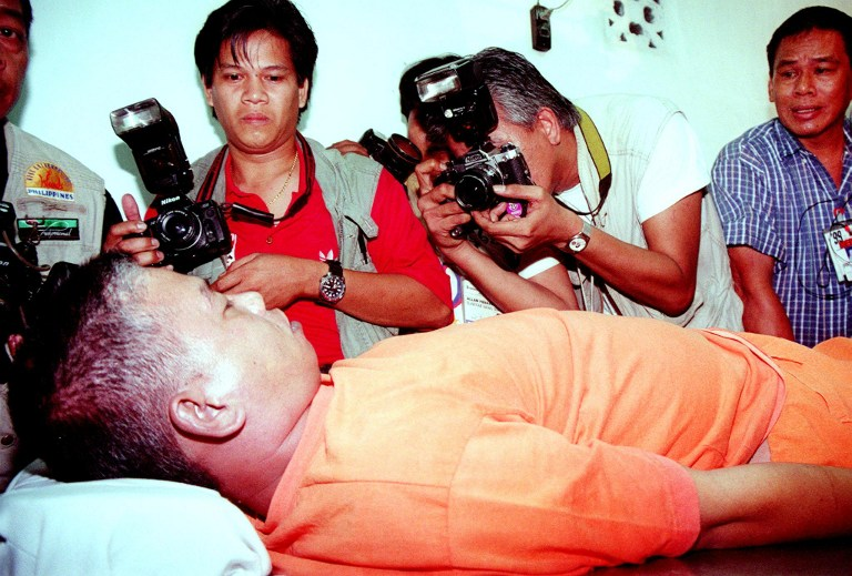 DEATH VIA LETHAL INJECTION. Photographers take pictures of the body of death convict Leo Echegaray after his body was transferred to a funeral morgue near Manila on February 5, 1999. File photo by Alex de la Rosa/AFP
