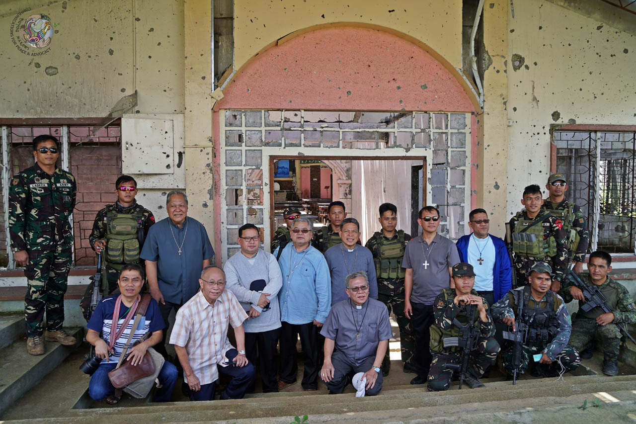 MILITARY ESCORT. Marawi Bishop Edwin de la Peu00f1a hopes to return again before the scheduled demolition of the church in June. Photo courtesy of DUYOG MARAWI
