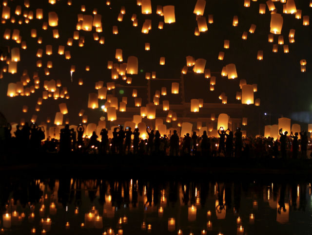 RELEASE TO THE SKY. A photo made available on 26 October 2014 shows Thais release thousands of hot air lanterns during the Yi Peng festival celebrations in Chiang Mai, northern Thailand, late 25 October 2014. The ancient northern traditional festival is held annually by launching floating lanterns into the night sky with the belief that misfortune will fly away with the lanterns as part of Loy Krathong celebrations. Photo by Pongmanat Tasiri/EPA